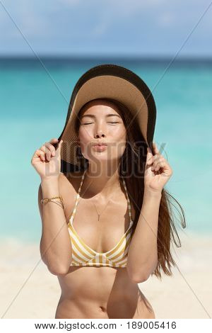 Cute Asian beach woman blowing a kiss holding floppy sun hat on beach vacation summer holidays wearing fashion golden stripes retro bikini outfit. Sepia vintage filter.