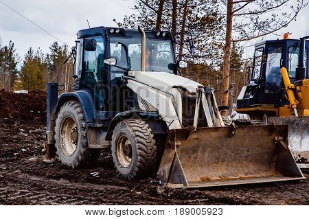 tractor loader is parked in the mud. Concept road construction.