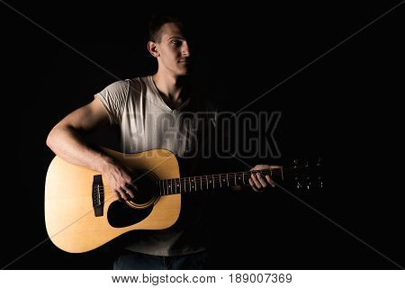Guitarist, Music. A Young Man Plays An Acoustic Guitar On A Black Isolated Background. Horizontal Fr