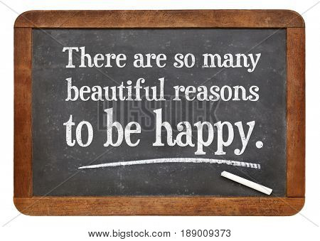 There are some many beautiful reasons to be happy - white chalk text on a vintage slate blackboard