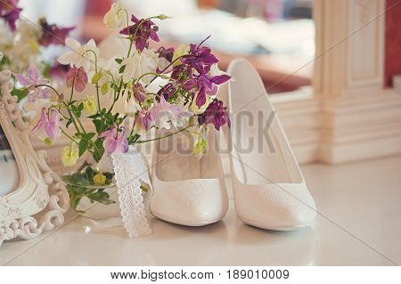 bridal bouquet of peones, wedding flowers for the ceremony on the chair in a hotel room with white shoes.