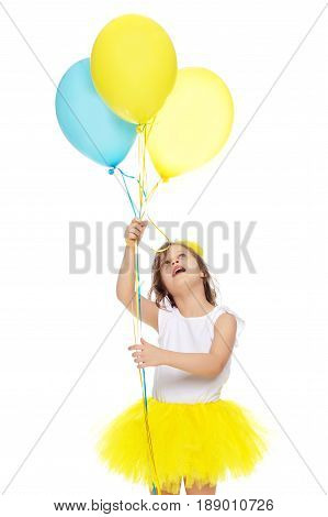 Pretty little blonde girl in a short bright yellow skirt and white blouse.Girl holds in hands balloons , She looks at them from the bottom up.Isolated on white background.