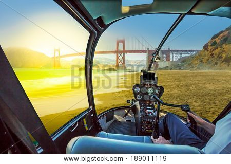 Helicopter cockpit inside the cabin on Golden Gate Bridge from Baker Beach at sunset on popular Baker Beach.Holidays, travel and leisure concept. San Francisco, California, United States.
