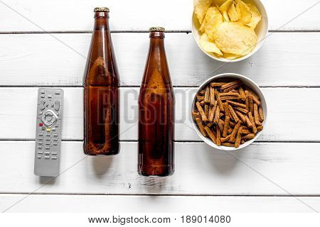 watching TV set with chips, beer and remote control on white background top view