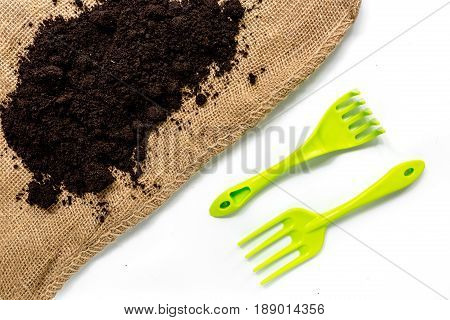 green garden tools and ground for planting flowers at home on white table background top view