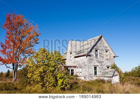 Old farm house decaying in rural countryside New Brunswick NB Canada