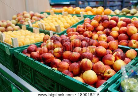 Peaches and apricots in plastic crates, supermarket food store