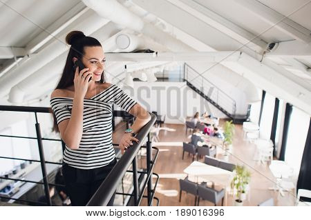 Young owner of a coffee shop or cafe is standing and talking on smartphone while smiling and looking away
