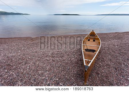 Canoe beached on gravel shore of calm Lake Superior water wilderness of Ontario ON Canada ready for an adventure trip outdoors