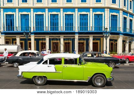 HAVANA,CUBA - MAY 29, 2017 : Street scene with vintage american cars in front of a new hotel in downtown Havana