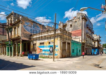 HAVANA,CUBA - MAY 29, 2017 : Street scene with people and decaying old buildings in Havana with an image of Che Guevara and a cuban flag painted on a wall