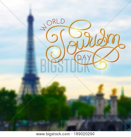 World tourism day hand lettering on blurred photo Eiffel tower, Paris, France background. Vector illustration for your design