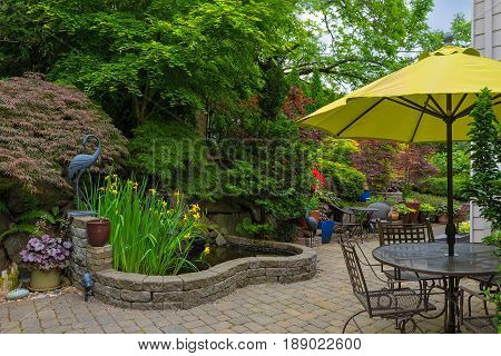 Home backyard hardscape and lush plants landscaping with garden furniture on paver brick patio