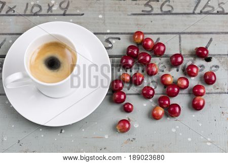 Black coffee in a cup with ripe coffee beans on the side
