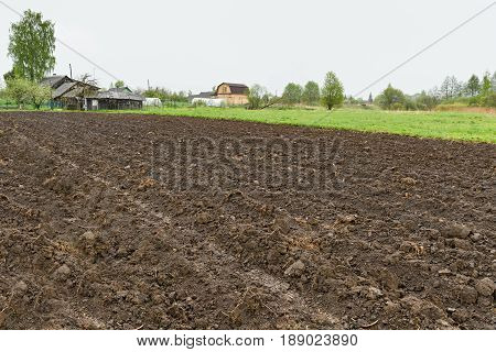 Ploughed Field And Some Village Houses Near It