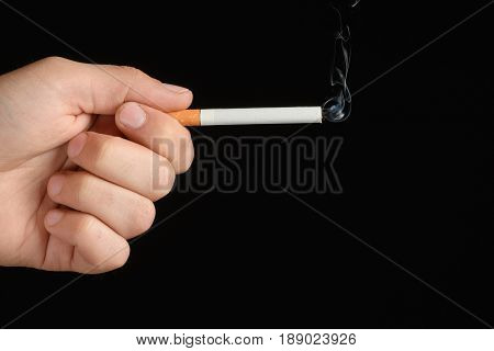 Man's Hand Holding A Smoke Cigarette Between Index Finger And Thumb In The Shape Of A Gun. Isolated