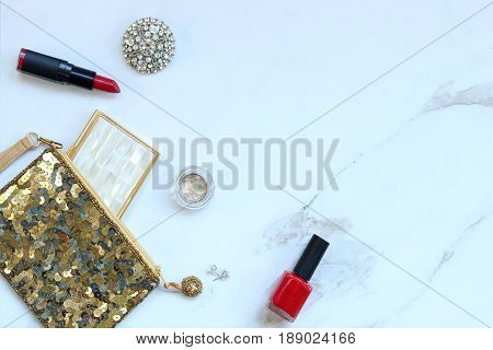 Gold sequined purse with beauty and fashion supplies spilling out. Red accents. White marble copy space.