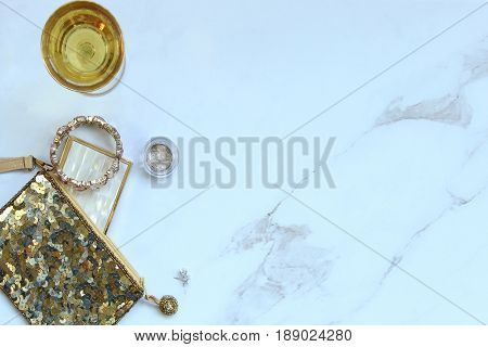 Gold sequined bag with fashion and beauty supplies spilling out onto white marble copy space. Champagne glass.