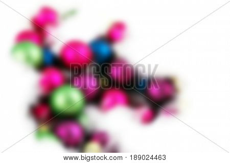Small Christmas ornaments nestled in a bed of feathers - blurred image background