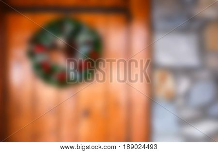 Christmas wreath hanging on a rustic wooden door - blurred image background