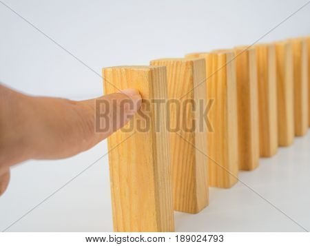 Concept of building success foundation. Chain Reaction In Business Concept Businessman Letting Or Preventing Dominoes Continuous Toppling On Rustic Wooden Desk