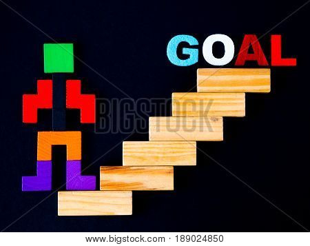 Concept of building success foundation. wooden block in the shape of human step on stacked wooden block like stairs to GOAL. Business development and growth concept on black background.
