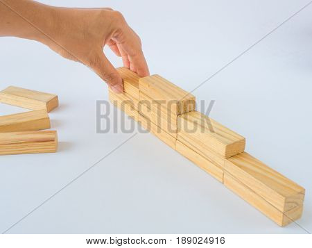 Concept of building success foundation. Women hand put wooden blocks on the stack of wooden blocks