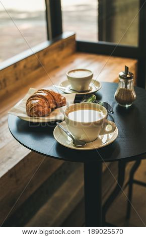 Coffee latte, cappuccino and croissant on small table in cafe, French or Italian breakfast concept
