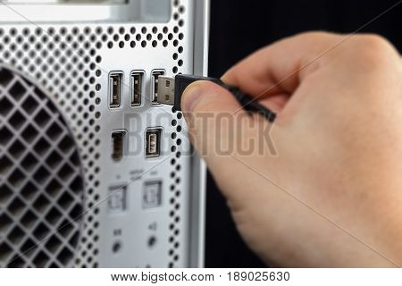 Hand connecting USB to the computer. Seen from near