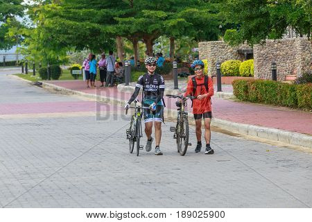 Khun Dan Prakan Chon Dam Nakorn Nayok Thailand - Apr 30.2017 : Two young cyclists with their bicycles walking together after bike touring at the dam friendship concept.