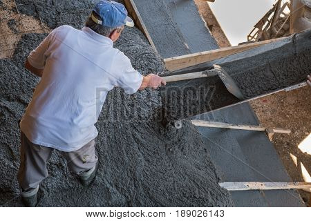 Worker spreading fresh concrete pouring from mixer's discharge chute