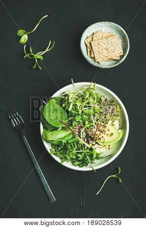 Green vegan breakfast meal in bowl with spinach, arugula, avocado, seeds and sprouts and crispy bread over black background, top view. Clean eating, dieting, vegan, vegetarian food concept