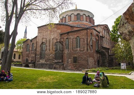 Istanbul,Turkey - May 7, 2017: People are sitting in front of  Hagia Irene, an eastern Orthodox church located in the outer courtyard of Topkapi Palace in Istanbul, Turkey.