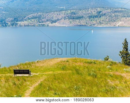Mountain hiking trail with bench overlooking the lake