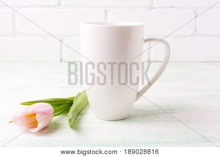 White coffee cappuccino mug mockup with tender pink tulip flower. Empty mug mock up for design promotion.