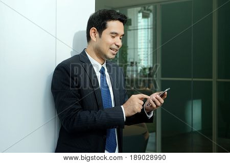 Business man using smart phone with happy smiling face standing in front of meeting room inside office building background businessman on smart phone on line conference concept