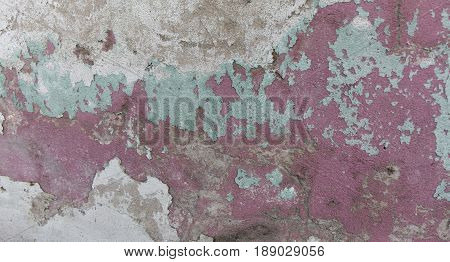 Old painted wall. Green and pink damage surface. Peeling paint background. Stone demaged backdrop