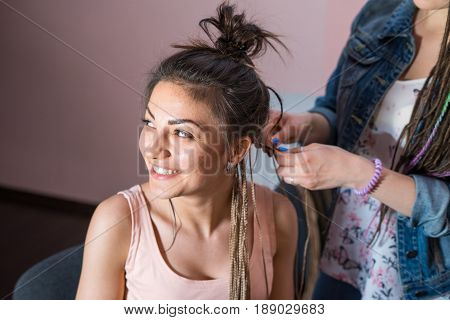 A hair stylist braids a young and beautiful girl. Zizi cornrows and dreadlocks plait