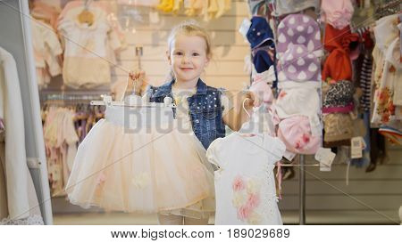 Shopping for kids. The lovely blonde girl shows the hangers with the outfits, which she chose