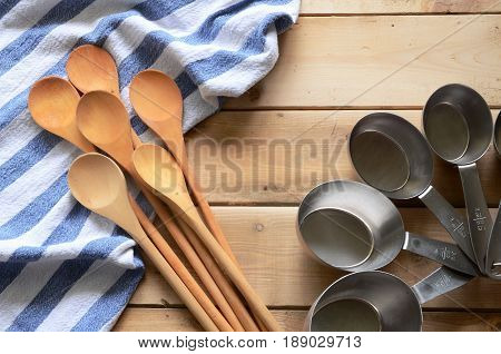 Wooden mixing spoons and tin measuring cups.