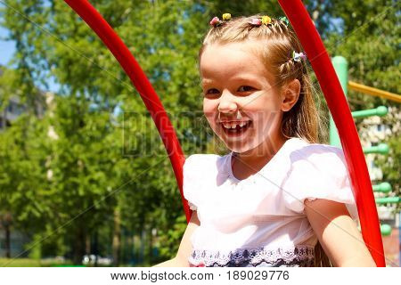 The Seven-year-old girl swinging on a swing