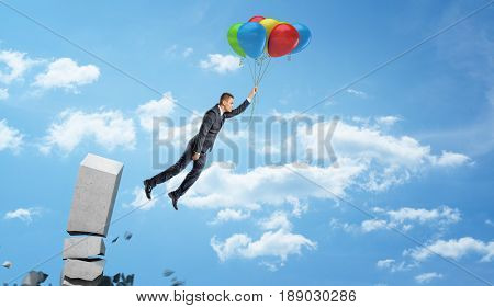 A businessman holding a set of colorful balloons on a string and flying away from a crumbling concrete column. New business options. Leave unprofitable market. Change business field.