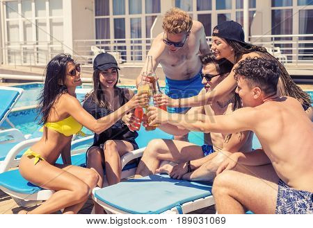 Cheers. Group of cheerful friends drinking cocktails and beer during party at the pool. They clink glasses and laughing