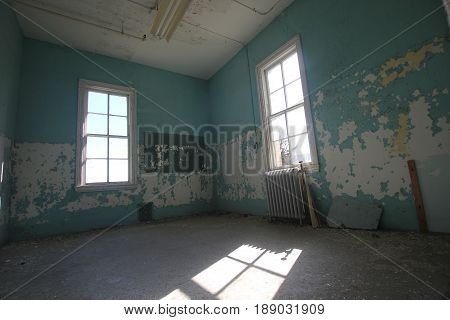 A room in an abandoned asylum with light pouring in.