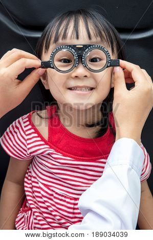 Asian Little Chinese Girl Doing Eyes Examination at An Optical Shop