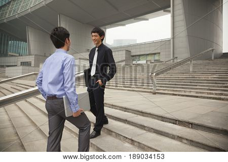 Chinese businessmen talking on city steps