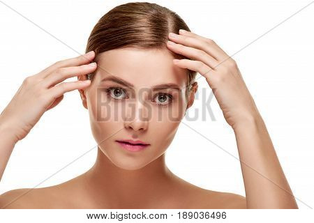 Beautiful sensitive woman with natural makeup touching her smooth facial skin