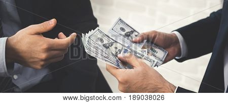 Businessman giving money US dollar bills to his partner - panoramic banner
