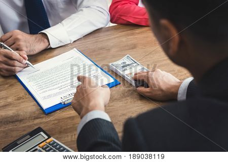 Businessman offering money and command to sign while making agreement - bribery and corruption concepts
