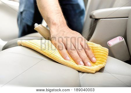 A man cleaning leather car seat with microfiber cloth - auto detailing and valeting concept